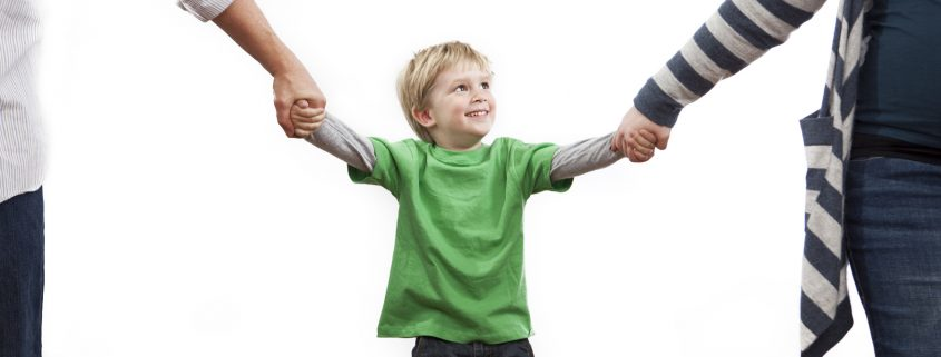 Little boy holding his mom and dad's hands. Shot in studio on a white background.