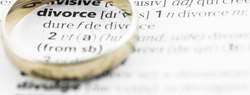 Divorce term text in macro from dictionary book, highlighted word with a gold wedding ring placed on printed white paper page. Concept of family, relationship difficulties, wedding and divorce law.